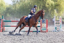Young woman riding horse on her course in show jumping equestrian competition