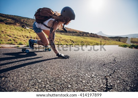 Young woman riding on her skateboard. Female skater practicing skating on country road.