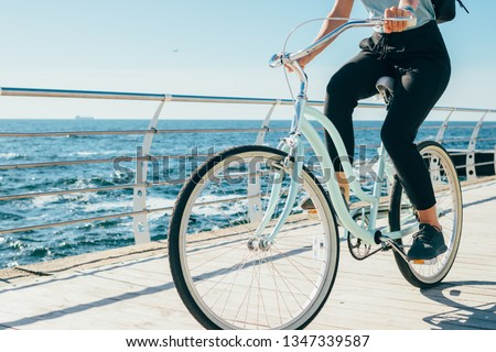 Young woman riding vintage bike along the waterfront. Female traveler with backpack cycling near sea on sunny summer day. #1347339587