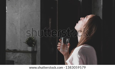 Young woman rinses her mouth with water while looking at mirror and spits water into the sink, side view.