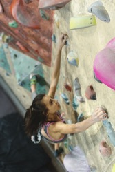 Young Woman Rock climber is Climbing At Inside climbing Gym. slim pretty Woman Exercising At Indoor Climbing Gym Wall. Focus on the hand. Concept of strength, sport, healthy lifestyle.