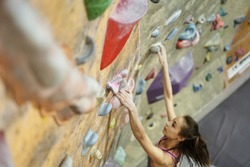 Young Woman Rock climber is Climbing At Inside climbing Gym. slim pretty Woman Exercising At Indoor Climbing Gym Wall. Slender fitness pretty woman making some hard moves and falling from last hold