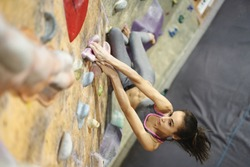 Young Woman Rock climber is Climbing At Inside climbing Gym. slim pretty Woman Exercising At Indoor Climbing Gym Wall. Slender fitness pretty woman concentrate on moves. Concept of strength, sport