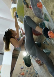 Young Woman Rock climber is Climbing At Inside climbing Gym. slim pretty Woman Exercising At Indoor Climbing Gym Wall. Concept of strength, sport, healthy lifestyle. Focus on feet.
