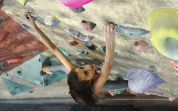 Young Woman Rock climber is Climbing At Inside climbing Gym. slim pretty Woman Exercising At Indoor Climbing Gym Wall. Slender fitness pretty woman making some hard moves