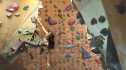 Young Woman Rock climber is Climbing At Inside climbing Gym. slim pretty Woman Exercising At Indoor Climbing Gym Wall. Concept of strength, sport, healthy lifestyle.