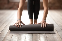 Young woman rolling black fitness or yoga mat before or after sport practice, working out at home in living room or in yoga studio. Healthy habits, keep fit, weight loss concepts. Close up view photo