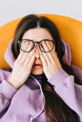 Young woman rubs her eyes after using glasses. Eye pain or fatigue concept.