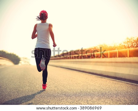 young woman runner athlete running at sunrise city road #389086969