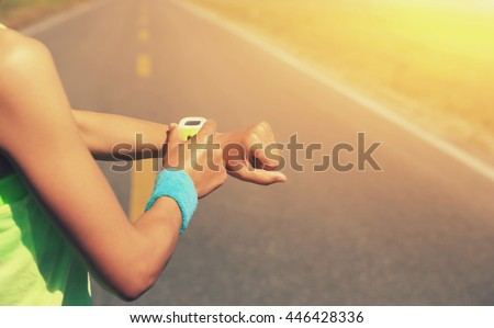 young woman runner ready to run set and looking at sports smart watch, checking performance or heart rate pulse trace. sport and fitness outdoors .