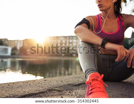 Young woman runner resting after workout session on sunny morning. Female fitness model sitting on street along pond in city. Female jogger taking a break from running workout. #314302445