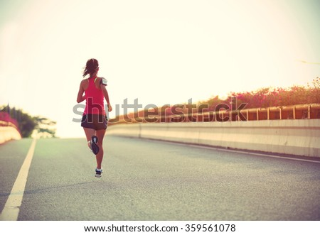 young woman runner running on city bridge road #359561078