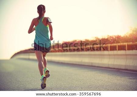 young woman runner running on city bridge road #359567696