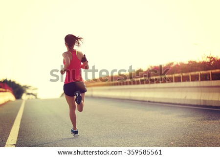 young woman runner running on city bridge road #359585561