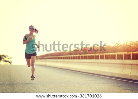 young woman runner running on...