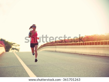 young woman runner running on city bridge road #361701263