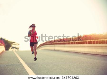 young woman runner running on city bridge road #361701263