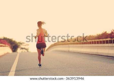 young woman runner running on city bridge road #363913946