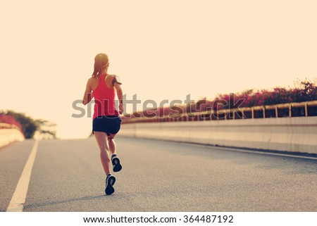 young woman runner running on city bridge road #364487192