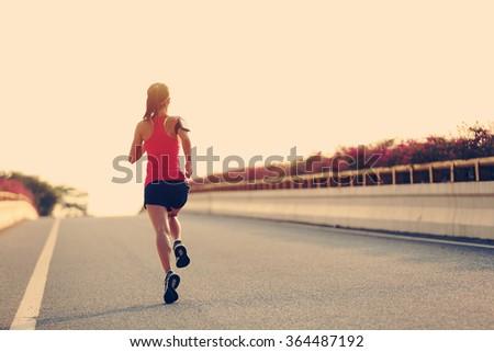 young woman runner running on city bridge road #364487192
