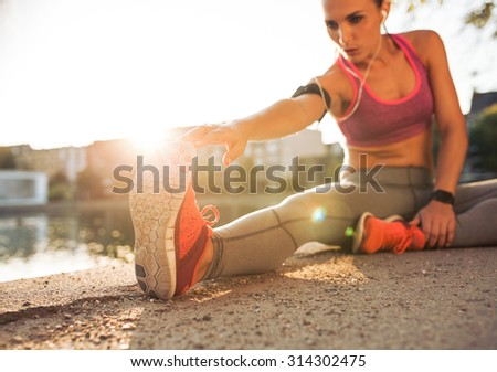Young woman runner stretching legs before doing her summer workout. Sportswoman warming up before outdoor workout.