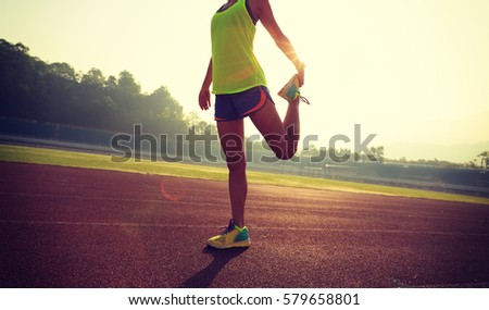Young woman runner stretching legs before run during sunny morning on stadium track