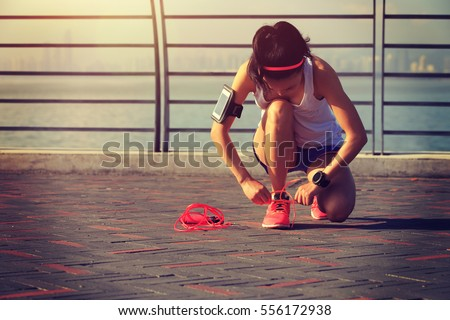 young woman runner tying shoelace at seaside #556172938