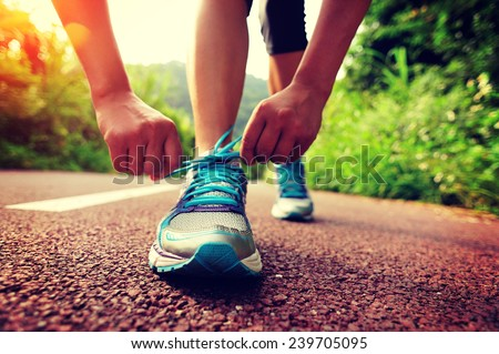 young woman runner tying shoelaces  #239705095