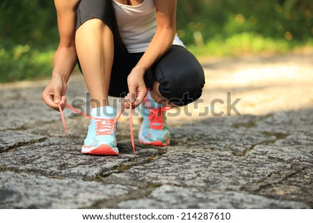 young woman runner tying shoelaces on stone trail #214287610