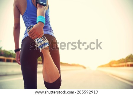 young woman runner warming up before run on city