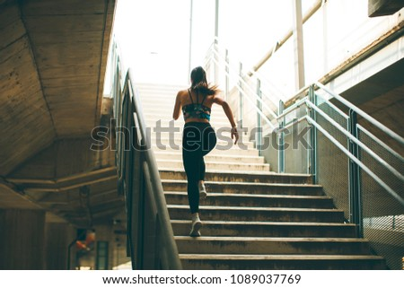Young woman running alone up stairs  outdoor #1089037769