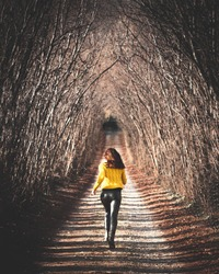 Young woman running away in a street surrounded by trees that creates a tunnel.