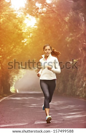 Young woman running Female runner jogging on misty road with the early morning at sunrise with sun breaking through the trees as she trains during a fitness workout