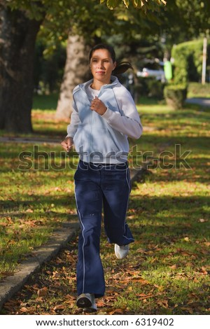 Young woman running in an autumn park.