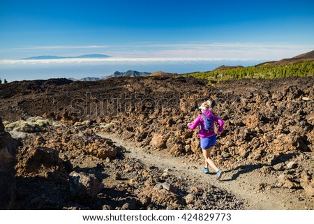 Young woman running in mountains on sunny summer day. Beauty female runner jogging and exercising outdoors in nature, trail running training on rocky trail footpath on Tenerife, Canary Islands #424829773
