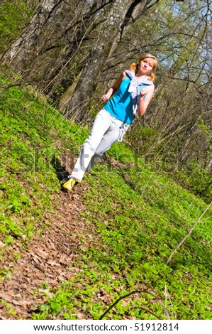 young woman running in spring forest