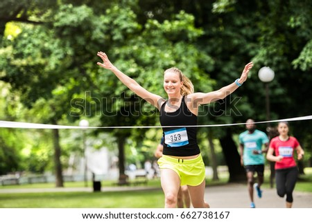 Young woman running in the crowd crossing the finish line. #662738167