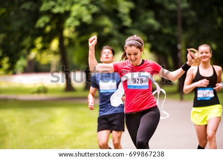 Young woman running in the crowd crossing the finish line. #699867238