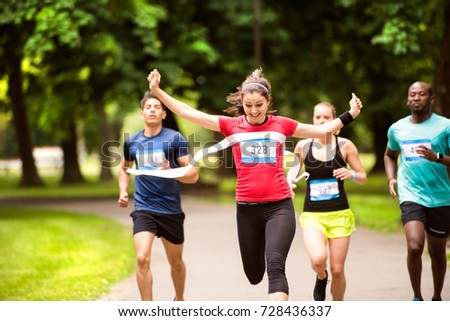 Young woman running in the crowd crossing the finish line. #728436337