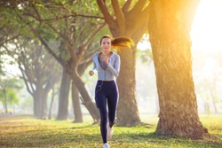 young woman running in the park at  morning