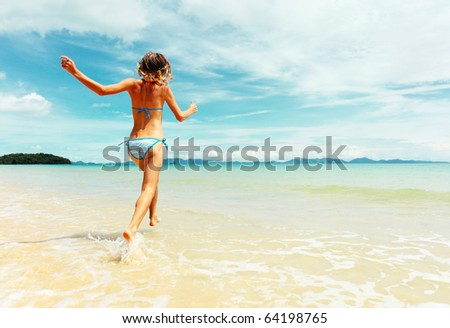Young woman running into sea