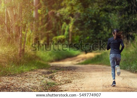 Young woman running on a trail running track with copy space, healthy lifestyle and sport concepts.