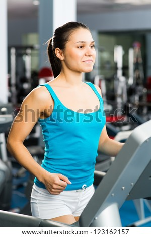 young woman running on a treadmill, exercise at the fitness club