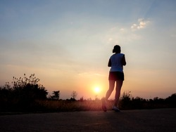Young woman running on rural concrete road on beautiful bright sunset sky background near summer field with copy space. Lifestyle evening run background. Fitness and healthy lifestyle concept.