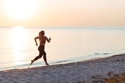 Young woman running on the beach at sunset