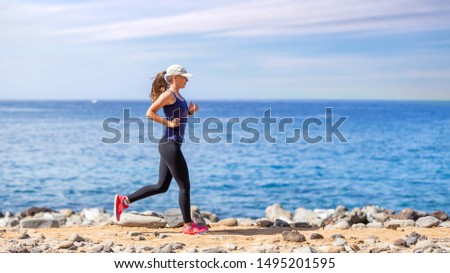 Young woman running on trail on the ocean coast. Healthy jogging lifestyle background