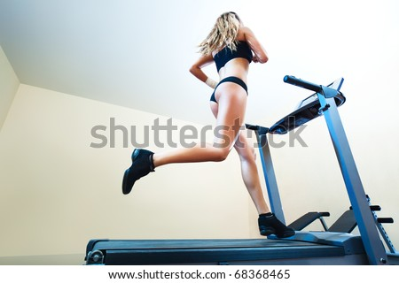 Young woman running on treadmill in gym.