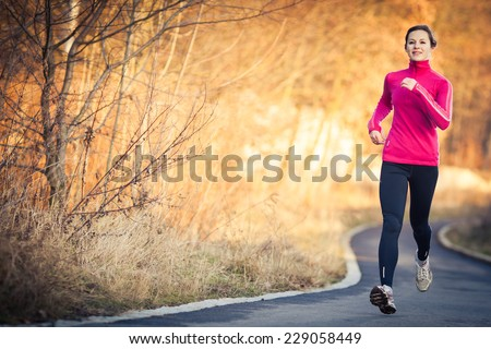 young woman running outdoors in ...