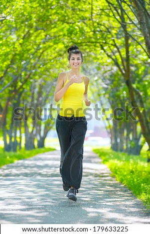 Young woman running outdoors in green park at lovely sunny summer day. Jogging