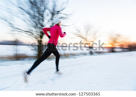 Young woman running outdoors on a cold winter day (motion blurred image)